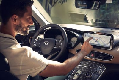A driver of the new Hyundai SANTA FE Plug-in Hybrid 7 seat SUV using the fully digital cluster.