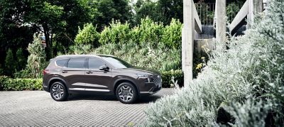 The new Hyundai SANTA FE Plug-in Hybrid 7 seat SUV parked in front of a modern house.